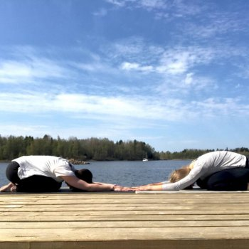 two women in a yoga pose on a pier