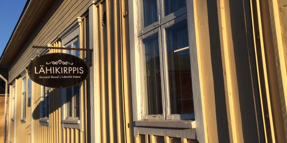 Lähikirppis's rustic sign on the wall of a yellow house in Old Raahe.